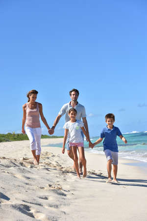 Family of four walking on a sandy caribbean beach
