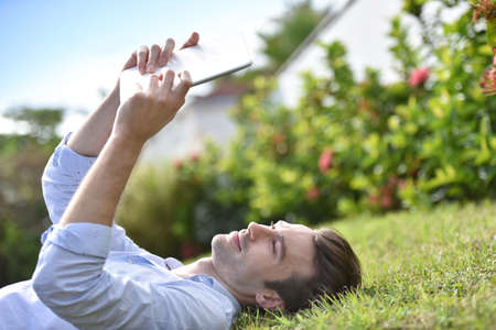 calm down: Man reading book on digital tablet, laid in grass