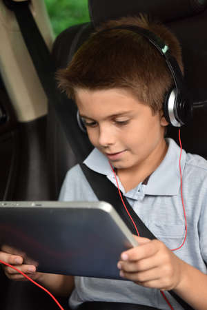 earphones: Kid watching moving on tablet inside car