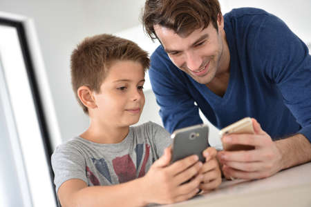 websurfing: Father and child playing with smartphones Stock Photo