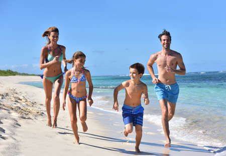 child swimsuit: Family runnning on a sandy beach in Caribbean island