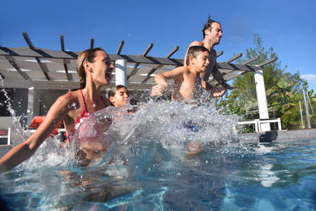 Family jumping into pool swimming-pool Stock Photo