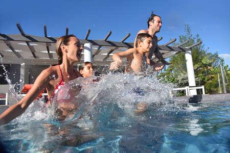 La familia que salta en la piscina piscina