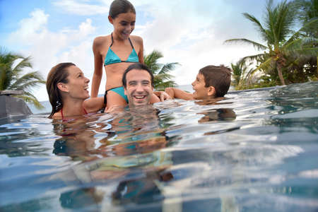 7 years old: Family of four enjoying swimming-pool