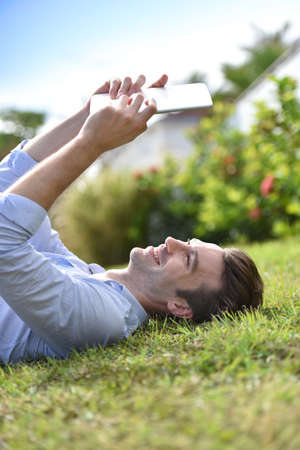 people relaxing: Man reading book on digital tablet, laid in grass