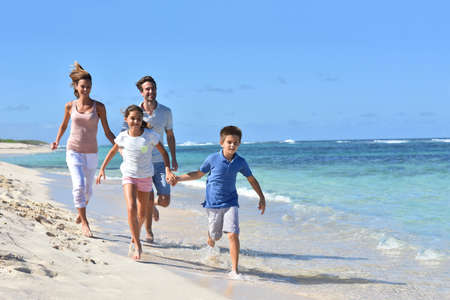 Family of four running on a sandy caribbean beach 免版税图像