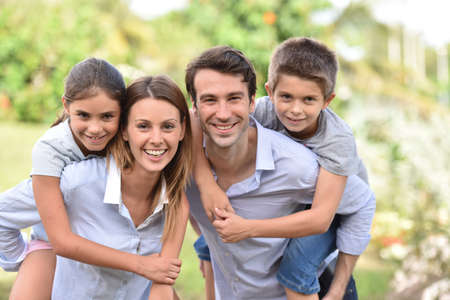 piggyback: Parents giving piggyback ride to kids outside Stock Photo