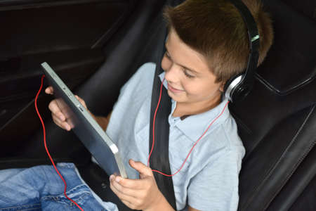 7 years old: Kid watching moving on tablet inside car