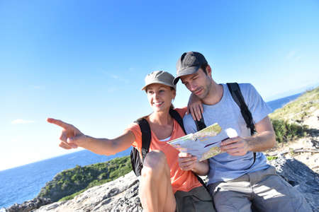caribe: Couple of hikers looking at map and scenery