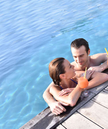 30 years old married couple: Couple drinking cocktail in swimming pool