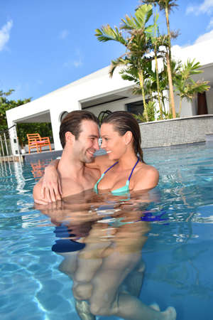 30 years old married couple: In love couple embracing in swimming-pool Stock Photo