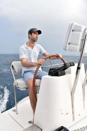 skipper: Skipper sitting at sailboat wheel