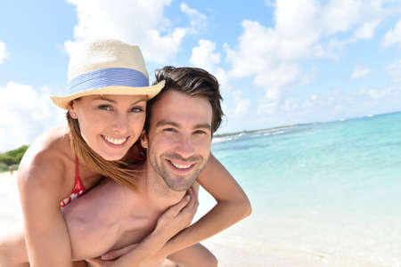 30 years old married couple: Man giving piggyback ride to girlfriend on Caribbean beach Stock Photo