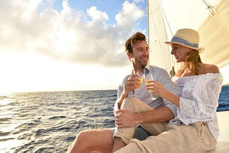 ロマンチックなカップルは日没でヨットを応援して