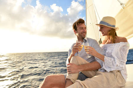 cruise: Romantic couple cheering on sailboat at sunset
