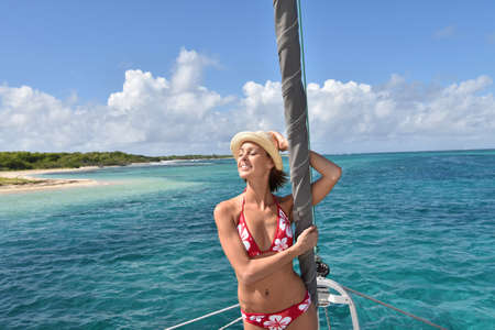 catamaran: Beautiful woman standing by catamaran mast Stock Photo