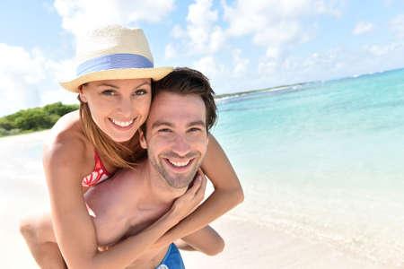 novio: Hombre que da a cuestas paseo a la novia en la playa del Caribe