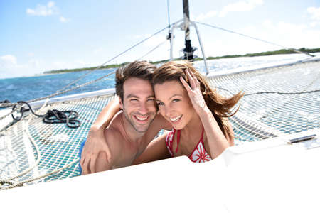 catamaran: Cheerful couple relaxing on catamaran net Stock Photo