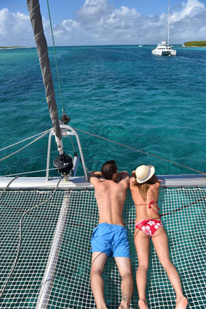 catamaran: Couple suntanning on a catamaran net