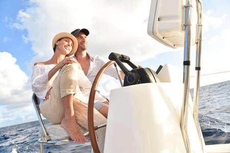 Paar op een zeilboot zitten aan wiel Stockfoto