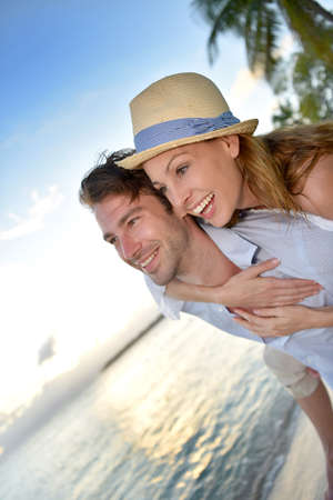 30 years old married couple: In love man giving piggyback ride to woman at the beach Stock Photo