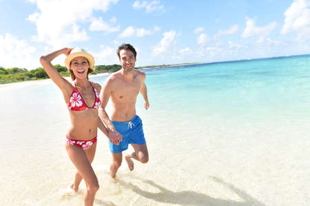 30 years old married couple: Cheerful couple running on a white sandy beach