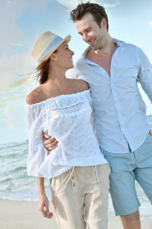 30 years old married couple: Happy just married couple walking on a sandy beach Stock Photo