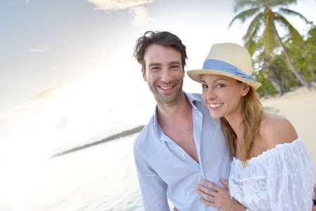 Feliz pareja de recién casados ??caminando en una playa de arena