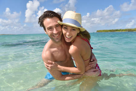 30 years old married couple: Cheerful couple in crystal caribbean sea