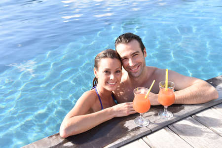30 years old woman: Couple drinking cocktail in swimming pool