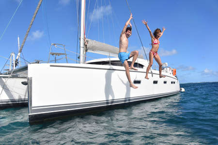 bikini couple: Cheerful couple jumping into water from boat