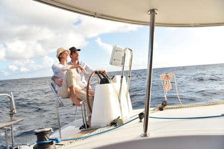 sail boat: Couple on a sailboat sitting at wheel Stock Photo