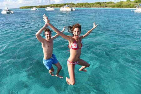 Wesoła para skoków do wody z łodzi