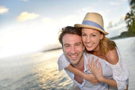 En el amor el hombre da a cuestas paseo a la mujer en la playa