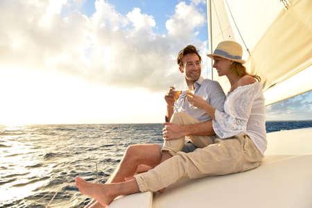 sailboats: Romantic couple cheering on sailboat at sunset