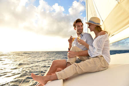 sail boat: Romantic couple cheering on sailboat at sunset