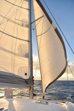 sail: Boat sails open with sunset Stock Photo