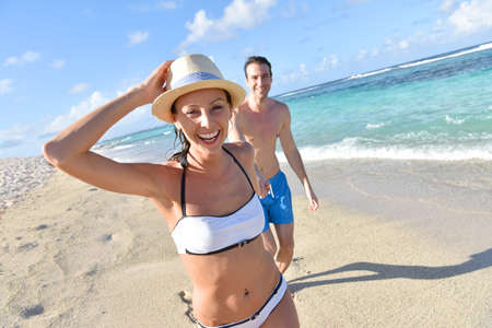 30 years old married couple: CHeerful couple running on sandy beach in Caribbean island
