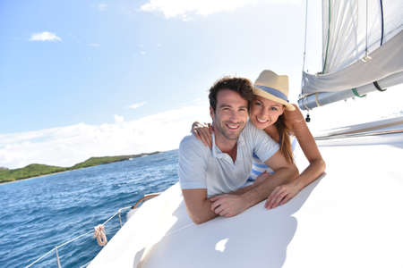 couple relaxing: Couple laying on a sailboat deck during cruise