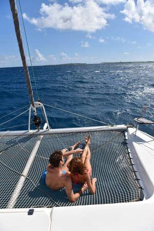 suntanning: Couple suntanning on a catamaran net