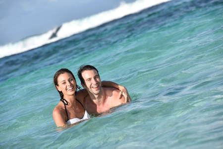 brunette woman: Cheerful couple enjoying sea bath in Caribbean island Stock Photo