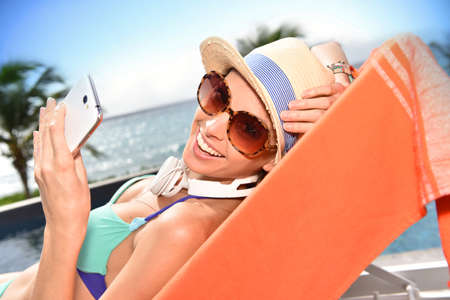 travel woman: Cheerful funny girl relaxing in long chair with smartphone