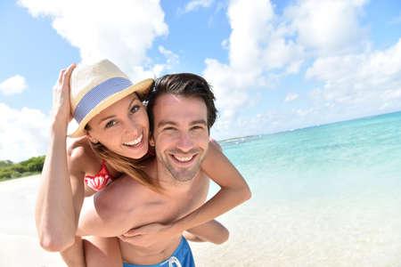 luna de miel: Hombre que da a cuestas paseo a la novia en la playa del Caribe
