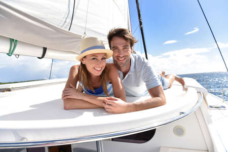 sail: Couple laying on a sailboat deck during cruise