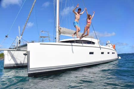 jumping: Pares alegres saltando en el agua de embarcación Foto de archivo