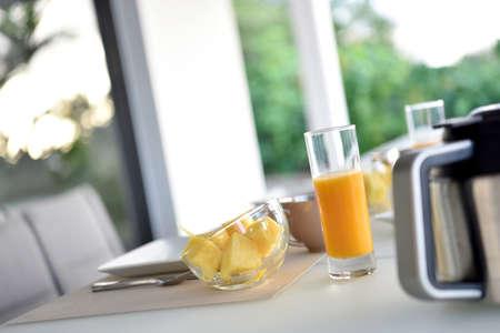 jugo de frutas: mesa del desayuno con un vaso de zumo de fruta