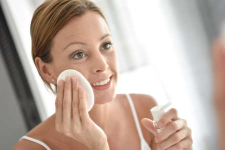 cleansing: Woman in bathroom cleansing face in front of mirror