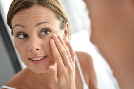 espejo: Mujer que aplica la crema facial en su cara
