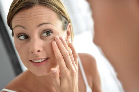 Vrouw toepassing gezicht crème op haar gezicht Stockfoto