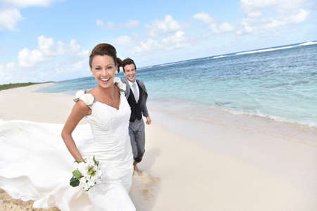 casados: Just married couple running on a caribbean beach